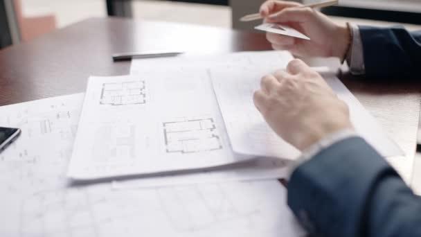 Detailní záběr ruce mužské architekta takže hause modrotisk v úřadu.