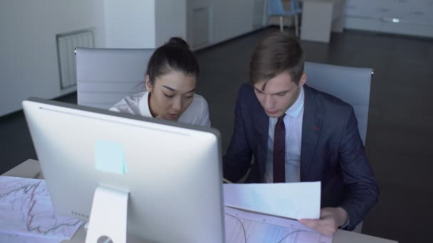 Two young employees are working, sitting at table with computer in large company, man and woman in business clothes discussing documents at desk in comfortable workplace. 4k
