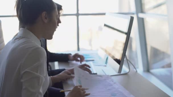 V kanceláři dva mladí lidé pracují s grafikou na papíře před počítačem. 4k