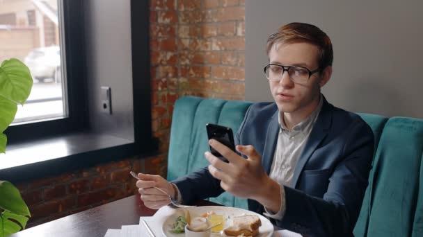 Porträt eines erfolgreichen Geschäftsmannes, der auf den Bildschirm seines Smartphones blickt und beim Frühstück im Café spricht.