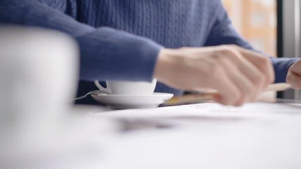 Mladí jistý podnikatel dokončí práci na projektu, pití kávy, sedí u stolu v útulné kavárně, osoba je v pracovním procesu, se těší voňavý nápoj