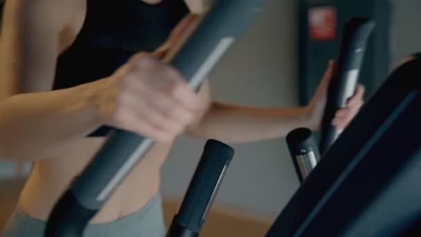 štíhlá sportovní mladá žena v tělocvičně cvičení na eliptické trenér cvičení detailní up.