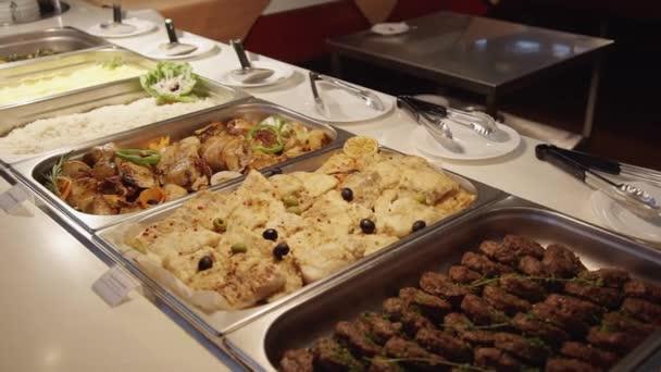 Různé vařené jídlo v nádobách pro bufet v interiéru moderní restaurace.