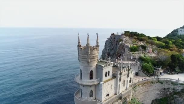aerial drove above view of swallow nest castle in yalta, crimea. flying over rocky blue sea shore