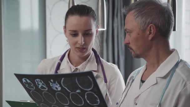 Male and female doctors working together looking at MRI image standing in hospital.