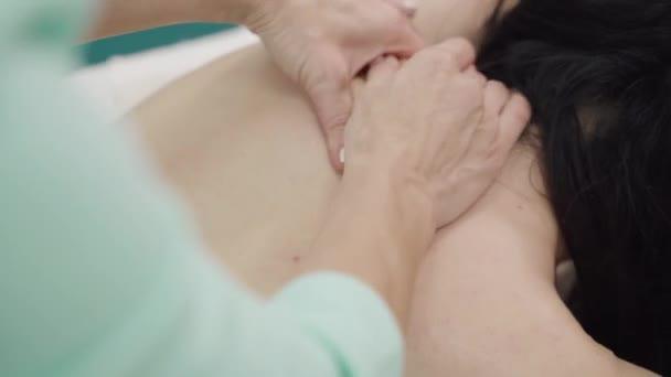 Relaxovaná žena dostává masáž zad v luxusních lázních s profesionálním masážním terapeutem. Wellness