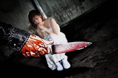 Murderer bloody hand holding knife smeared with blood ready to a