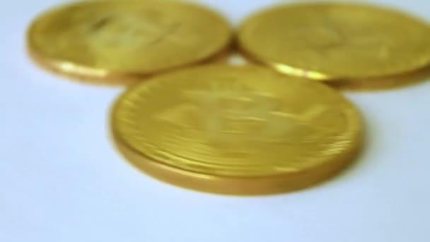 drei Goldmünzen Bitcoins, Drehen auf weißem Hintergrund Nahaufnahme