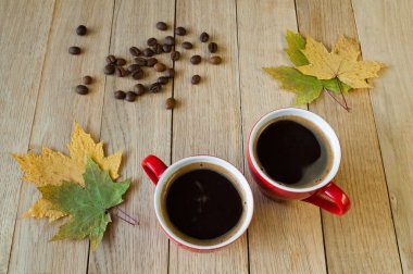 Two cups of coffee with autumn leaves and coffee beans on a wood