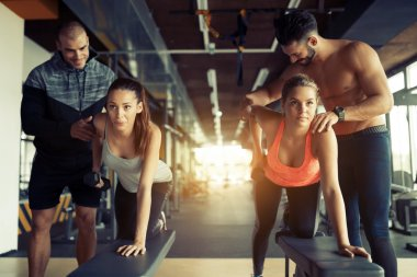 Personal trainers giving instructions in gym