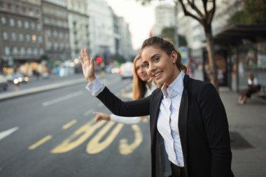 Businesswomen hailing taxi