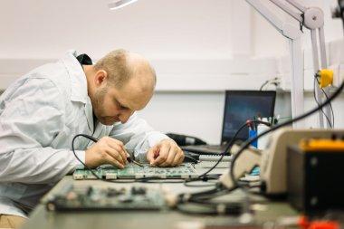 Technician fixing motherboard by soldering