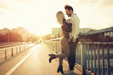Couple kissing and dating on bridge