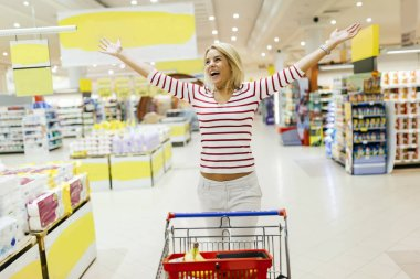 Woman jumping from joy in supermarket