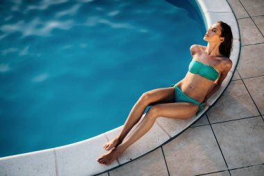 Woman sunbathing at swimming pool