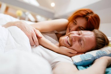 Beautiful couple smiling in bed