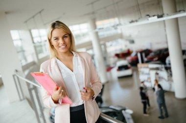 beautiful blonde woman at car dealership