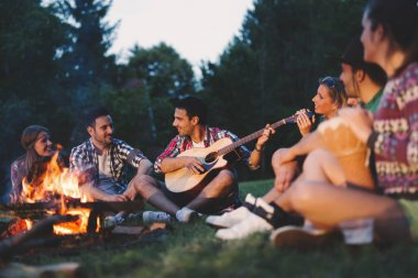 Happy friends playing music in nature