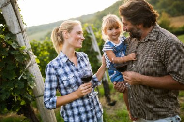 Winegrower family tasting wine
