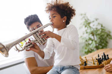 Girl with her father learning trumpet