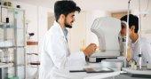Pozorný optik zkoumání pacientka na štěrbinovou lampu