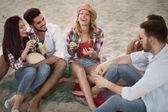 Skupina mladých veselých přátel mít skvělý čas na pláži