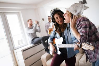 Young beautiful happy dancing girls playing guitar and partying