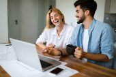 Pohledný mladý muž a atraktivní žena pracovat společně na laptop