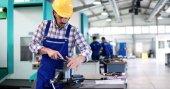 Fotografie Industrie Arbeiter arbeiten an CNC-Maschine in Metallindustrie Fabrik