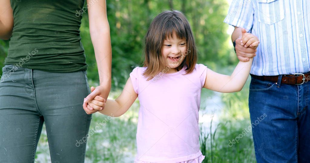 Beautiful little girl with down syndrome walking with parents in nature