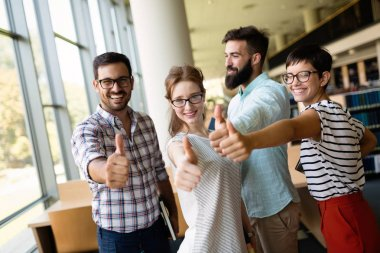 education concept - happy team of students showing thumbs