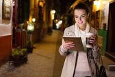 Fényképek Vonzó fiatal nő segítségével a digitális tábla és a kávéfogyasztás