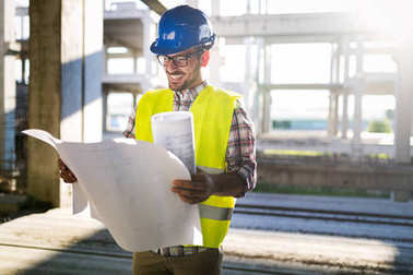 Picture of construction site engineer looking at construction plan