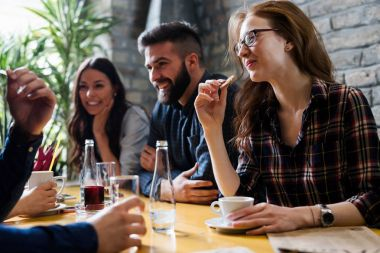 Happy young friends hangout together in coffee shop