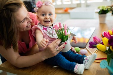 Happy mother's day. Child daughter congratulates moms and gives her flowers