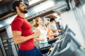 Schönen jungen Mann tun Cardio-Training auf Laufband im Fitness-Studio