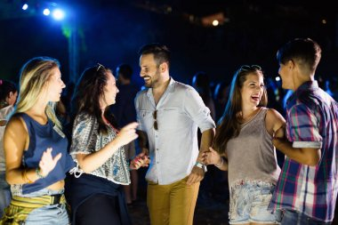 Group of young happy friends having fun time together at music festival