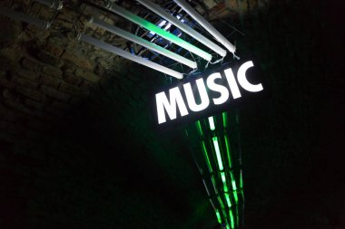 Bright lights in night club with white neon music sign