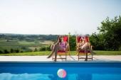 Fotografie Beautiful women relaxing and sunbathing in resort