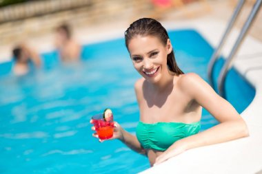 Sunbathing woman enjoying cocktail and swimming pool