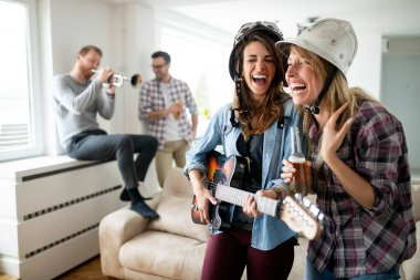 Group of Friends having fun and partying in house and playing music