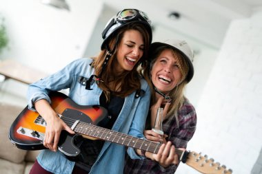 Cheerful group of friends having party together and playing instruments