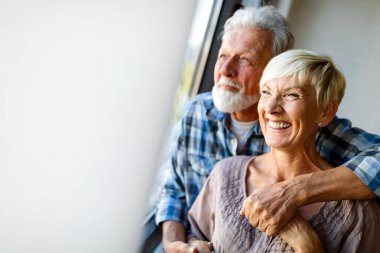 Happy smiling senior couple in love hugging and bonding with true emotions at home