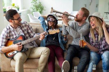 Friends at home enjoying singing and playing guitar, having fun