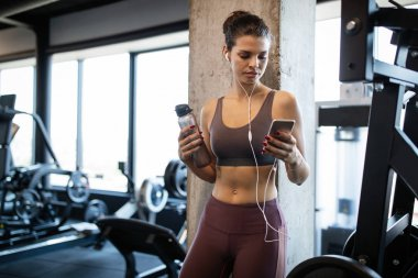Young fit woman at the gym relaxing and listening to music using a mobile phone