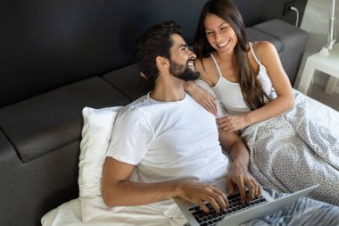 Happy young couple using laptop on bed at bedroom stock vector