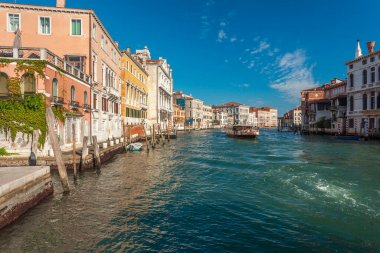 Venice, Italy - August 16, 2018: View of narrow Canal with boats and gondolas in Venice