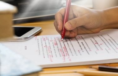 hand holding red pen over proofreading text