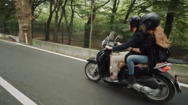 Slow motion side shot (60 fps) of young Caucasian couple riding their scooter on beautiful country road through forest