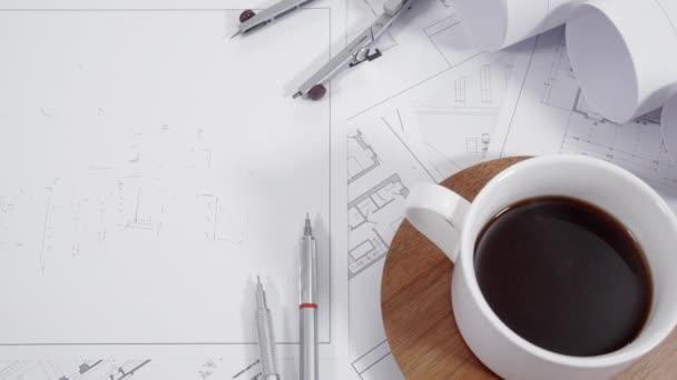Detailní záběr architektonických výkresů na stole